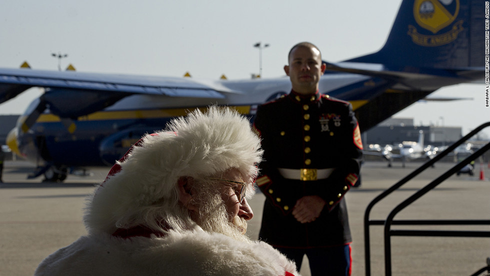 Santa Claus, aka Tim Connaghan, sits in the audience while a Marine stands guard during a presentation at Ronald Reagan National Airport on Monday, December 3, as part of the Marines' Toys for Tots program. Thousand of donated toys are set to be delivered to families affected by Hurricane Sandy.