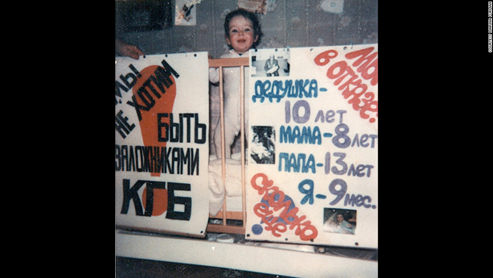 "The night before the Furmans took a final stand, their 9-month-old daughter Aliyah posed with posters, made by family friends. The one on the left reads in Russian, ""We don't want to be hostages of KGB!"""