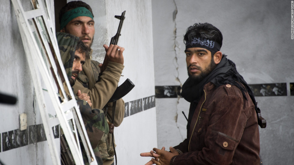 Rebel soldiers stand guard inside a building in Aleppo on December 6.