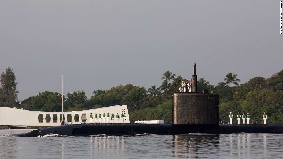 The USS Tucson performs a pass in review near the USS Arizona Memorial in Pearl Harbor, Hawaii.