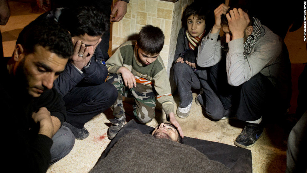 Syrians mourn a fallen rebel fighter at a rebel base in the al-Fardos area of Aleppo on December 8, 2012.