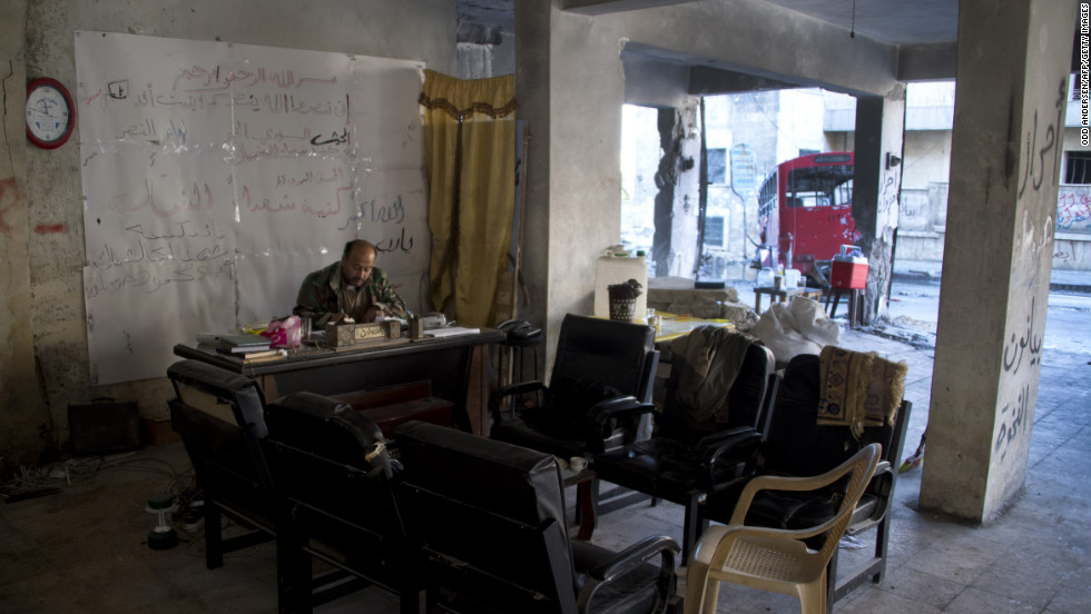 A Syria rebel commander sits behind a desk in his bombed-out position in Aleppo on December 8.