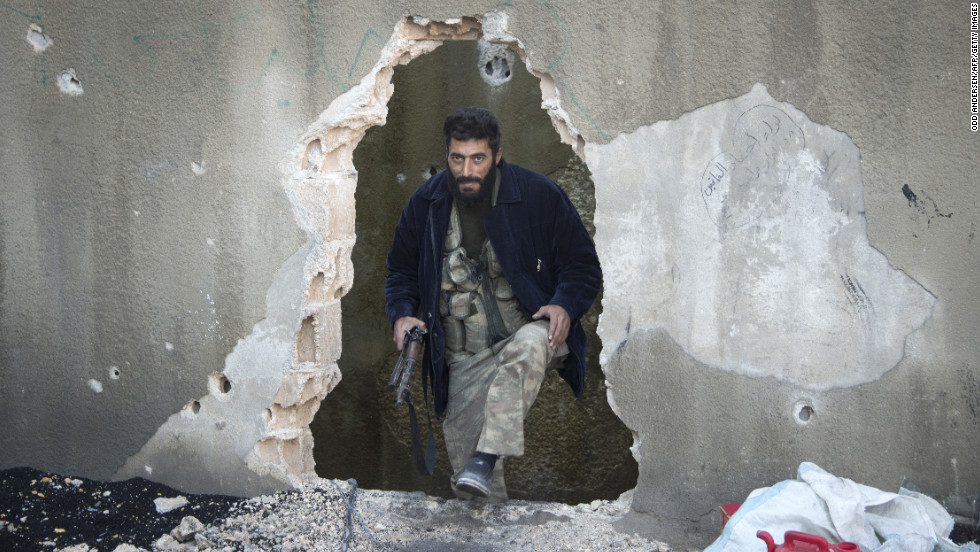 A Syrian rebel fighter emerges from a hole in a wall in Aleppo on December 8.