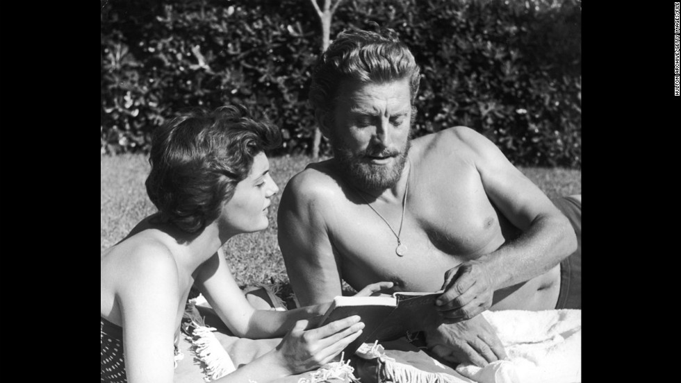 Kirk Douglas looks at a book with his second wife, Anne Buydens, circa 1956. The two married in 1954.