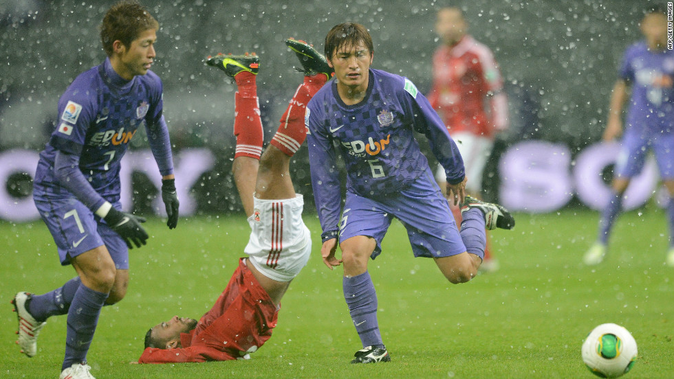 Al-Ahly midfielder Hossam Ashour takes a tumble as he fights for the ball with Sanfrecce Hiroshima's Toshihiro Aoyama (right) and Koji Morisaki (left) in the snowy conditions.