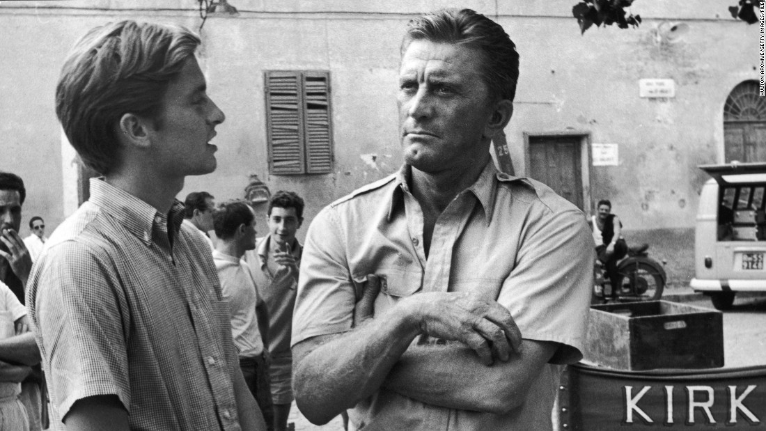 "Kirk Douglas appears with his son Michael on the set of the film ""Cast a Giant Shadow"" in Rome in the mid-'60s. Michael Douglas had a small uncredited role in his dad's move. He would go on to become a major film star himself in the 1980s and '90s."