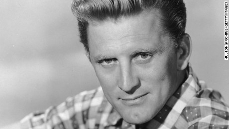 circa 1955:  Studio portrait of American actor Kirk Douglas resting one arm on his knee and wearing a checkered short-sleeved shirt.  (Photo by Hulton Archive/Getty Images)