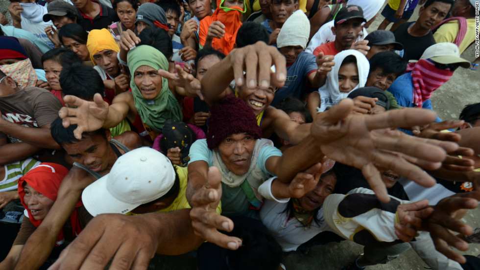 Victims of Typhoon Bopha jostle for position as they beg for relief food in New Bataan in Compostela Valley province on Sunday, December 9.