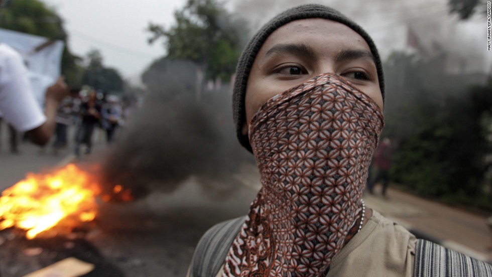 An Indonesian student stands in front of burning tires during a protest to mark Human Rights Day in Jakarta, Indonesia, on December 10.