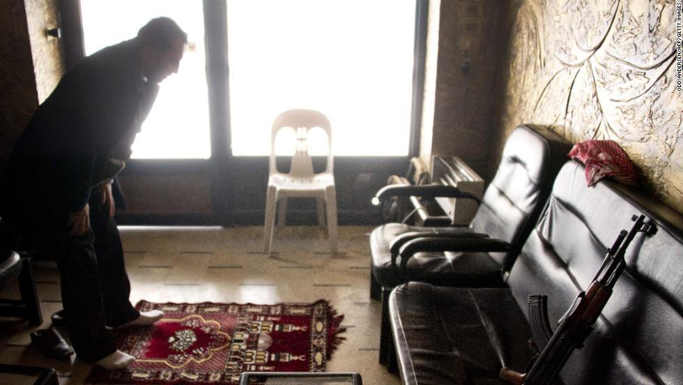 A rebel soldier prays in a shop in Aleppo on December 9.