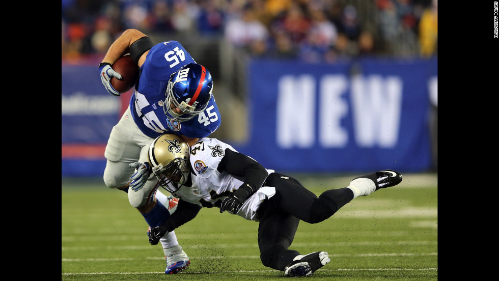 Saints safety Roman Harper knocks over Giants fullback Henry Hynoski on Sunday.