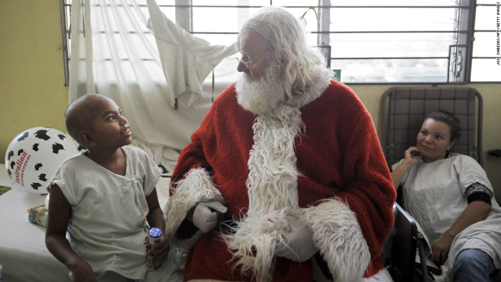 Icelandic philantropist Einar Sveinsson, dressed as Santa Claus, speaks with a patient in the oncology ward during a visit to the Benjamin Bloom National Children's Hospital in San Salvador, El Salvador, on Tuesday, December 11.