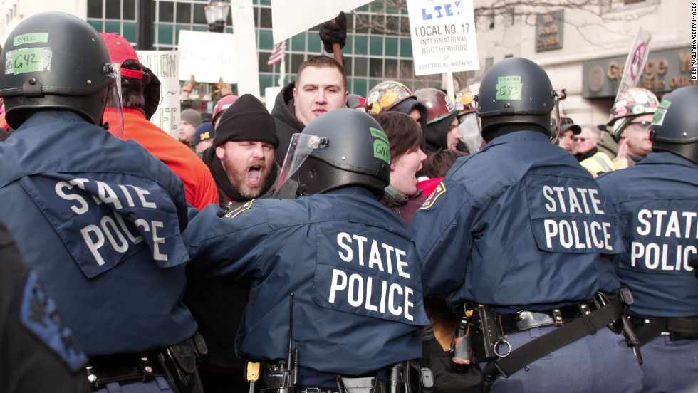 Michigan State Police in riot gear push back against protestors during a rally against right-to-work legislation at the Michigan State Capitol on Tuesday, December 11, in Lansing, Michigan. The House approved two controversial right-to-work measures that would weaken unions' power.