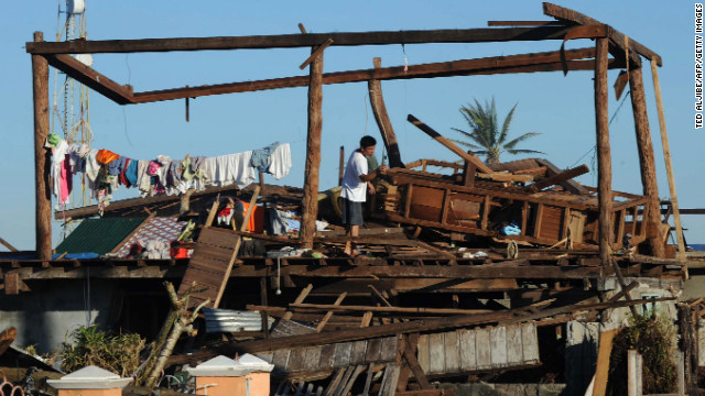 A resident stands on his destroyed house in Cateel town on December 11.