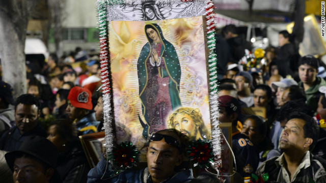 Pilgrims hold an image of Guadalupe Virgin before the birthday of the Guadalupe Virgin at the Basilica de Guadalupe in Mexico City on December 11, 2012. Mexicans celebrated the appearance of the Virgin of Guadalupe to Juan Diego in 1531. AFP PHOTO/Alfredo Estrella (Photo credit should read ALFREDO ESTRELLA/AFP/Getty Images)