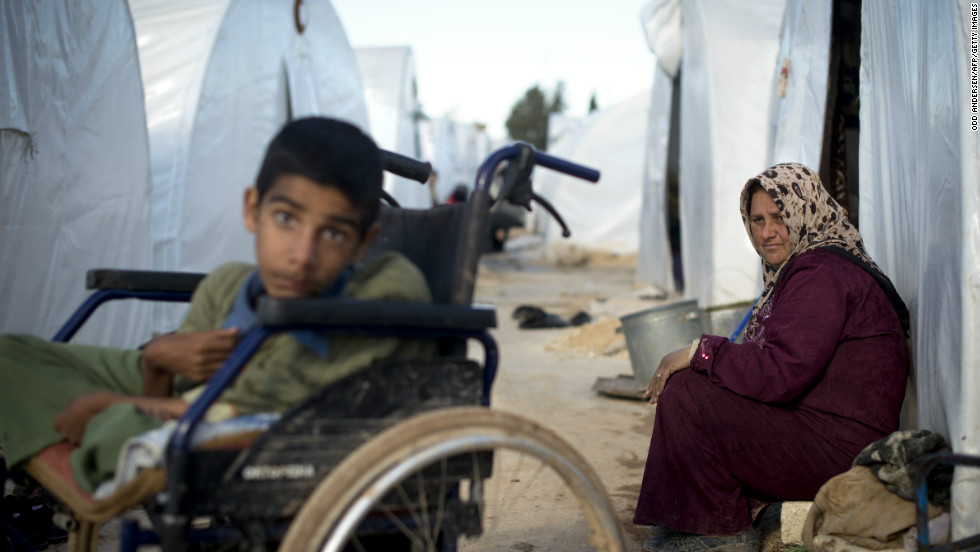 A mother looks over at her disabled child sitting among plastic tents in a refugee camp on the border between Syria and Turkey near the northern city of Azaz on December 5, 2012.