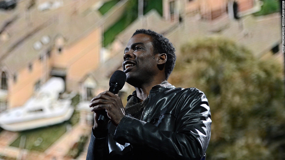 Chris Rock addresses the crowd at Madison Square Garden in front of projected images of Sandy's devastation.