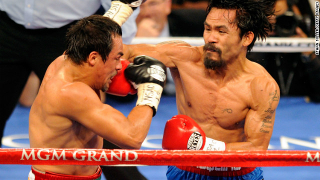 Manny Pacquiao (R) throws a right at Juan Manuel Marquez during the fourth round of their WBO world welterweight title fight at the MGM Grand Garden Arena November 12, 2011 in Las Vegas, Nevada.