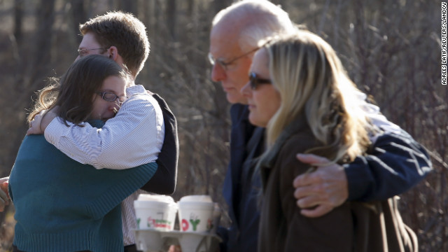 Family members embrace each other outside Sandy Hook Elementary School after a shooting on December 14.