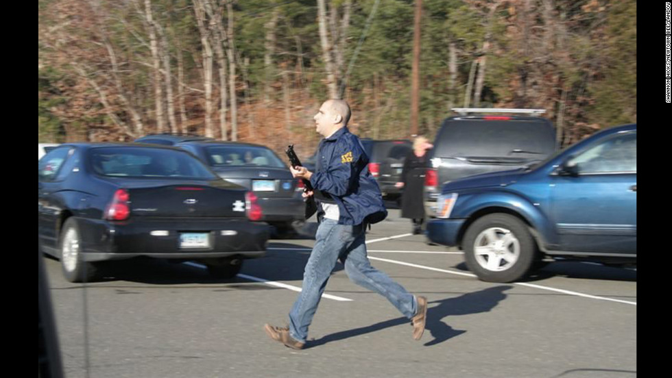 A Connecticut State Police officer runs with a shotgun at the Sandy Hook Elementary School in Newtown on December 14.