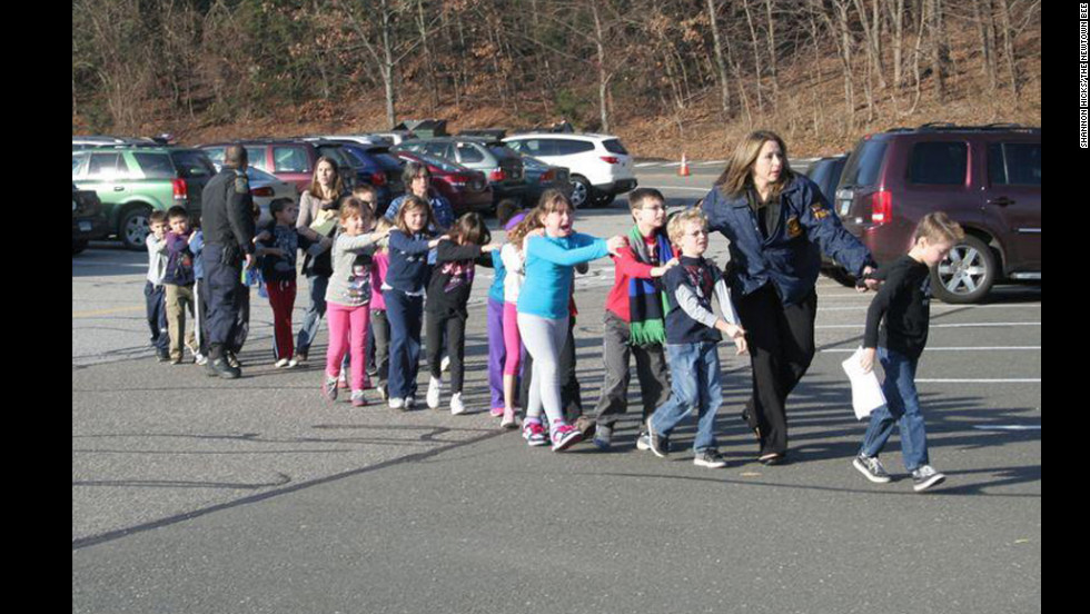<strong>December 14: </strong>State police personnel lead children away from Sandy Hook Elementary School in Newtown, Connecticut. A gunman killed 18 children and six adults at the school before he died; two more children died later at a hospital.