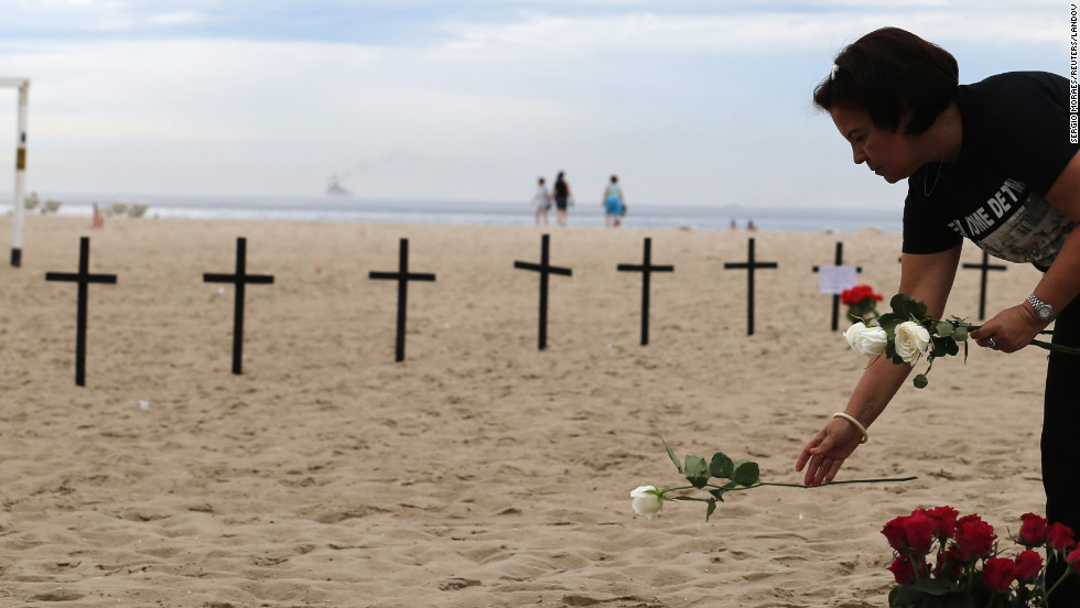 A woman puts a flower near crosses planted by Rio de Paz (Rio of Peace), in memory of the victims of the Sandy Hook Elementary school shooting on Copacabana beach in Rio de Janeiro on Saturday.