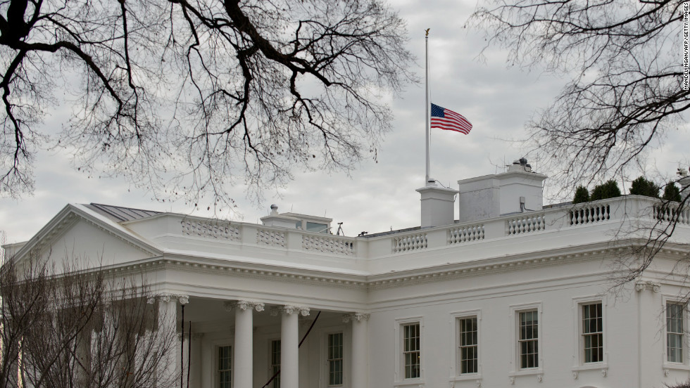 The U.S. flag flies at half-staff above the White House on Saturday.