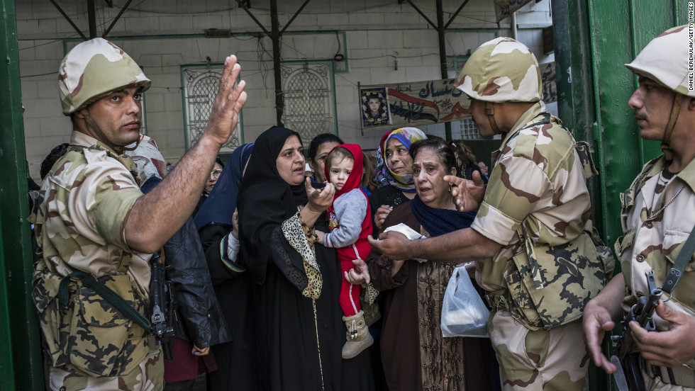 Soldiers check the identity of voters as Egyptian women line-up to cast their vote on December 15, 2012 in Cairo, Egypt.