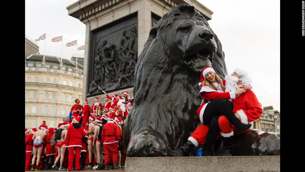 Revelers in Santa costumes sit on the lion statue at the base of Nelson's Column in London's Trafalgar Square on December 15.