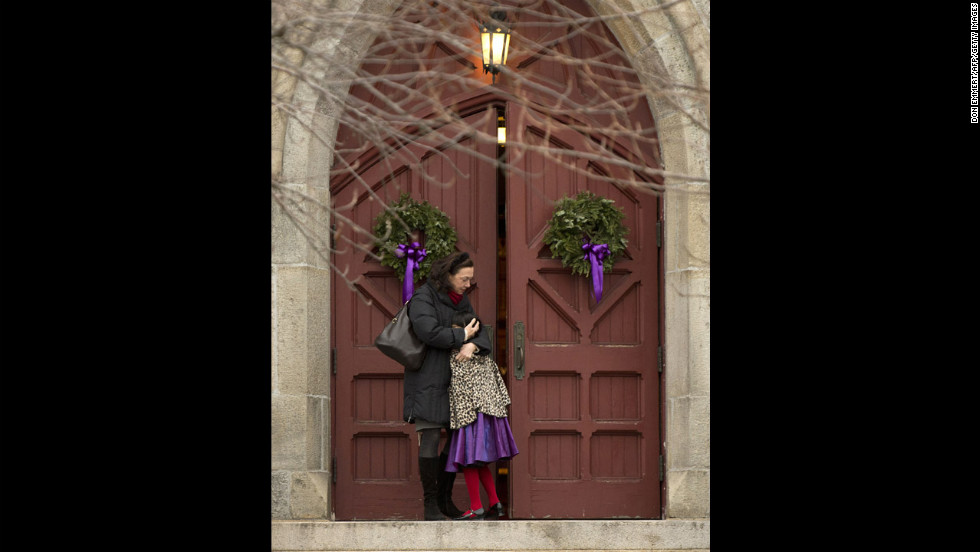 A woman hugs her daughter on the steps of Trinity Church on December 16 in Newtown.