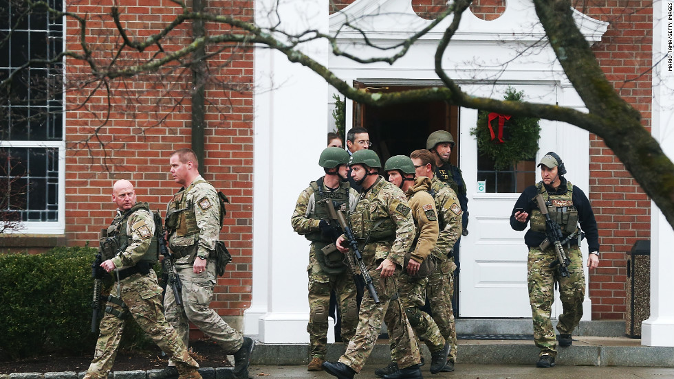 Connecticut State Police officers walk out of St. Rose of Lima Roman Catholic Church after the Newtown church received a threat December 16.