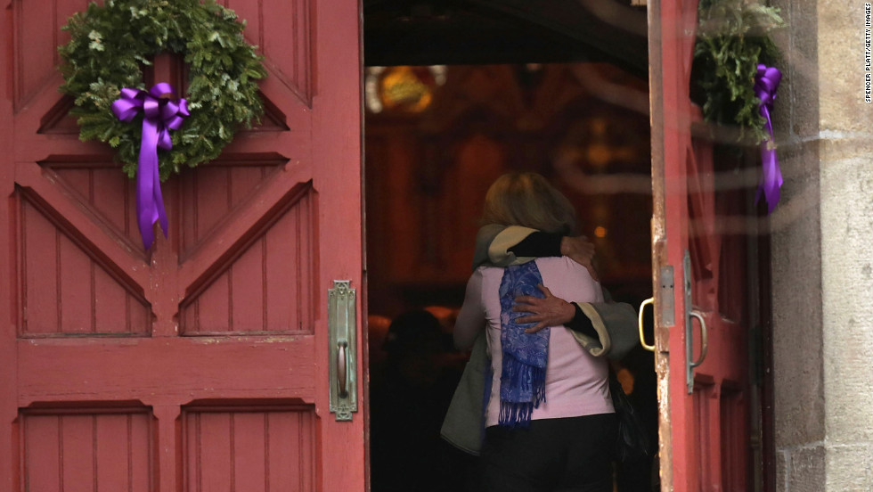 A woman receives a hug as she leaves morning service December 16 at Trinity Church in Newtown near the elementary school.
