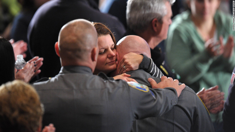 A woman comforts a law enforcement officer at Sunday night's interfaith prayer vigil.