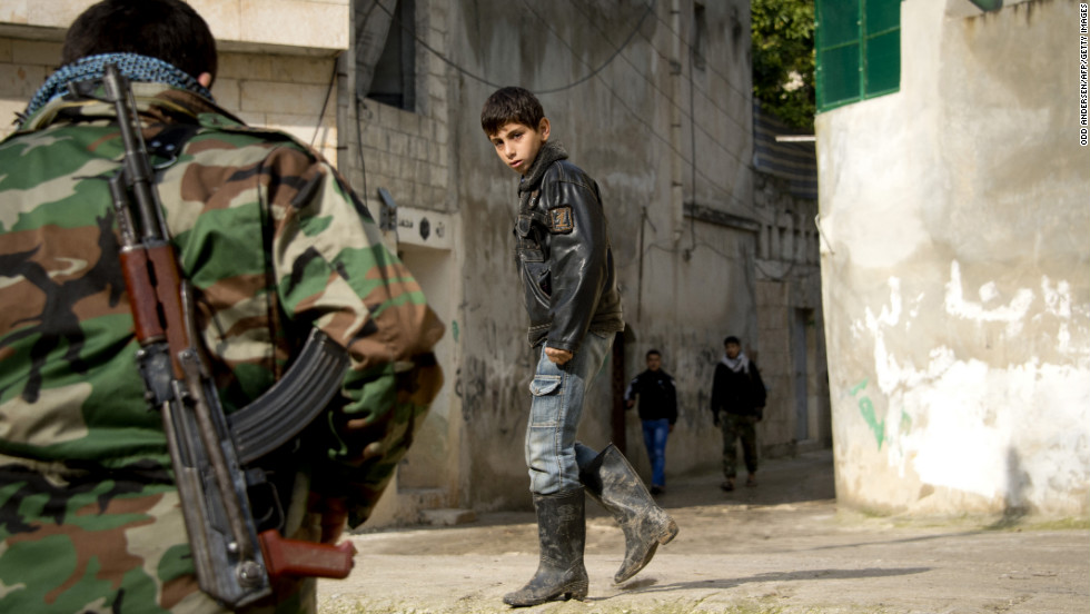 A Syrian boy walks past a rebel fighter in the northern town of Darkush, Syria, on Friday, December 14.