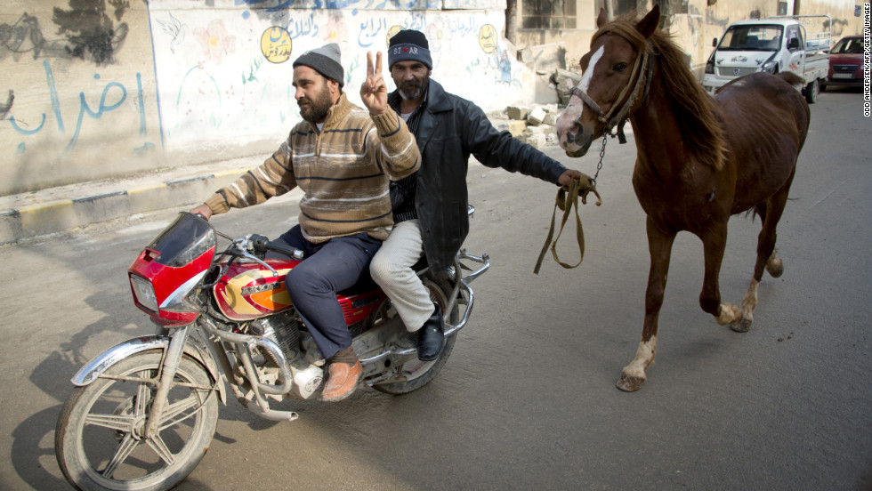 Two men on a motorcycle lead a horse through the northern town of Darkush, Syria, on December 14, 2012.