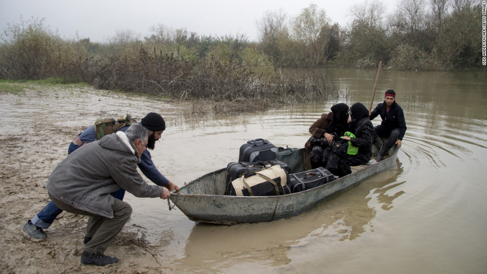 Rebel fighters push out a boat carrying two Syrian women fleeing to Turkey through the Orontes River near the northern Syrian town of Darkush on December 14.