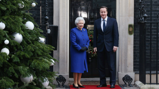 British Prime Minister David Cameron (R) greets Her Majesty Queen Elizabeth II as she arrives at Number 10 Downing Street to attend the Government's weekly Cabinet meeting on December 18, 2012 in London, England.