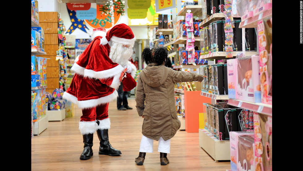 A girl points out toys to Santa Claus on Saturday, December 15, in a store in Lille, France.
