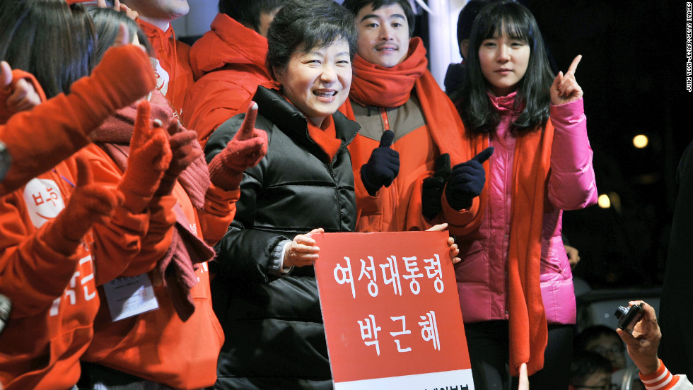 South Korea's presidential candidate Park Geun-hye of the ruling New Frontier Party holds a placard reading 'Woman President Park Geun-hye' during her election campaign in Seoul on December 18, 2012. If she wins, she will be the first woman leader of the country.