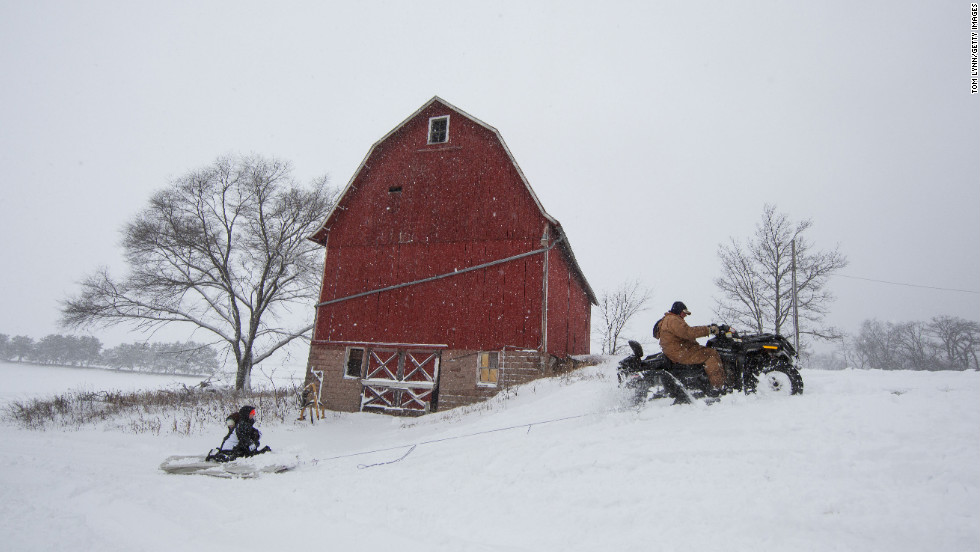 Abby Moon and Carley Moon are pulled on a mattress by their grandfather Clyde Moon's four-wheeler during a winter storm in Fairfield, Wisconsin, on Thursday, December 20.  The blizzard cut power to tens of thousands of homes and forced schools to close across the upper Midwest.