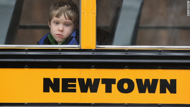 A child gazes from a school bus as it passes by the St. Rose of Lima Catholic church while mourners gathered for a funeral service for shooting victim Jessica Rekos, 6, on December 18, 2012 in Newtown, Connecticut. Four days after 20 children and six adults were killed at Sandy Hook Elementary School, most students in Newtown returned to school. Children at Sandy Hook Elementary will attend a school in a neighboring town until authorities decide whether or not to reopen their school.