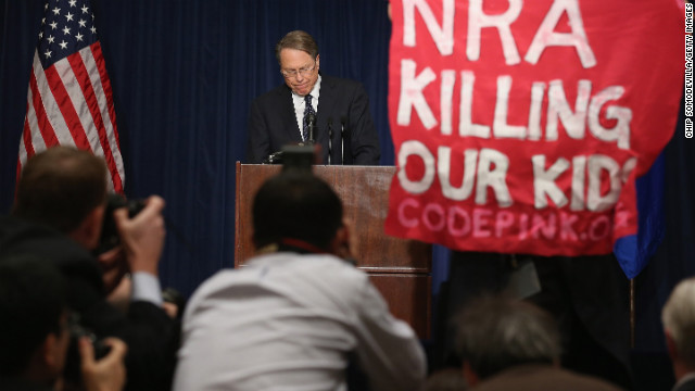 WASHINGTON, DC - DECEMBER 21:  A demonstrator from CodePink holds up a banner as National Rifle Association Executive Vice President Wayne LaPierre delivers remarks during a news conference at the Willard Hotel December 21, 2012 in Washington, DC. This is the first public appearance that leaders of the gun rights group have made since a 20-year-old man used a popular assault-style rifle to slaughter 20 school children and six adults at Sandy Hook Elementary School in Newtown, Connecticut, one week ago.  (Photo by Chip Somodevilla/Getty Images)