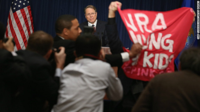 A demonstrator from CodePink holds up a banner as National Rifle Association Executive Vice President Wayne LaPierre delivers remarks during a news conference at the Willard Hotel December 21, 2012 in Washington, DC. This is the first public appearance that leaders of the gun rights group have made since a 20-year-old man used a popular assault-style rifle to slaughter 20 school children and six adults at Sandy Hook Elementary School in Newtown, Connecticut,
