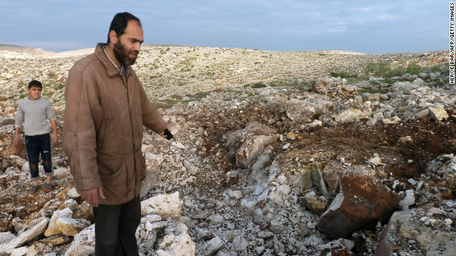 Syrian men point towards a crater where they said a Scud missile landed near the military base of Sheikh Suleiman on the outskirts of the northwestern town of Darret Ezza on December 13, 2012.