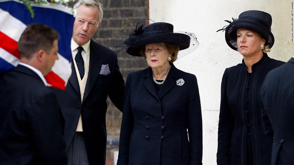Thatcher, with her son, Mark, and her daughter, Carol, watches the coffin of her husband, Denis, during his funeral in July 2003 in London. Denis Thatcher died at age 88.