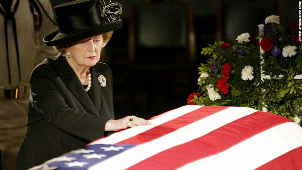 "Thatcher touches the flag-draped coffin of Reagan as he lies in state in the U.S. Capitol Rotunda in June 2004.  In a prerecorded video at his funeral, she called Reagan ""a great president, a great American and a great man."" ""And I have lost a dear friend,"" she said."