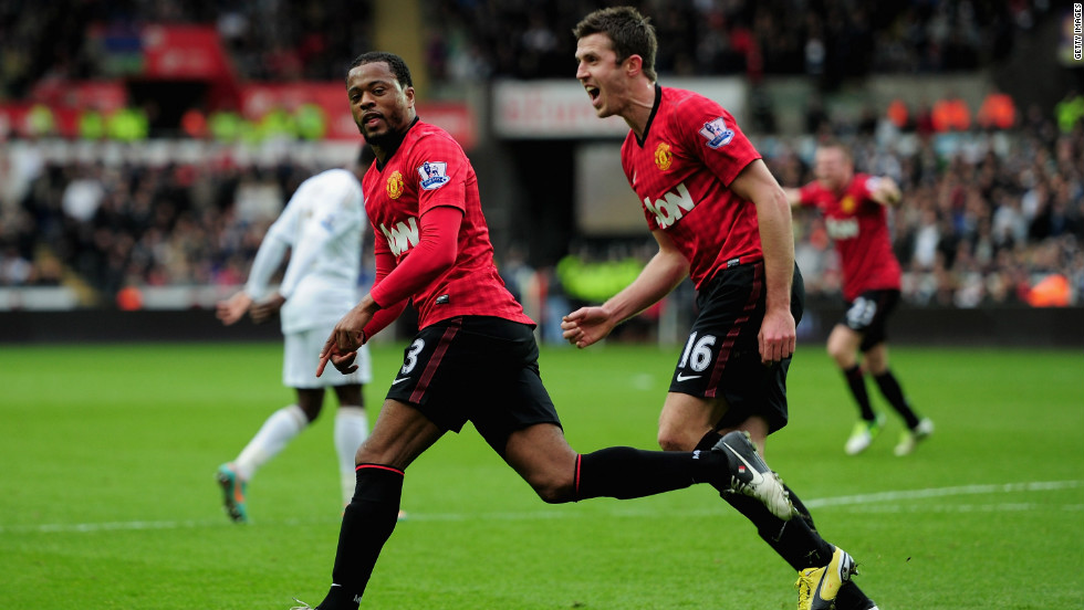 Evra races away to celebrate with teammate Michael Carrick in hot pursuit as the league leaders make the perfect start in Wales.