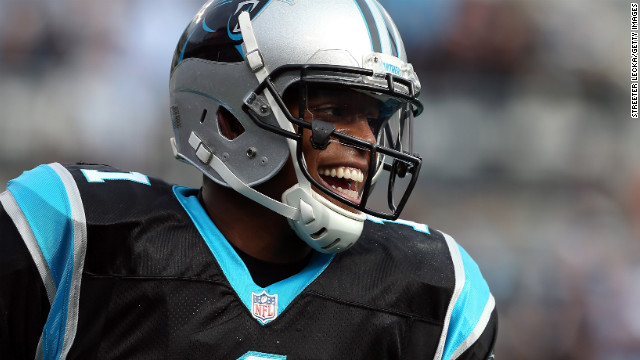 Cam Newton of the Panthers reacts after throwing a touchdown pass to teammate Steve Smith during their game against the Raiders on Sunday.