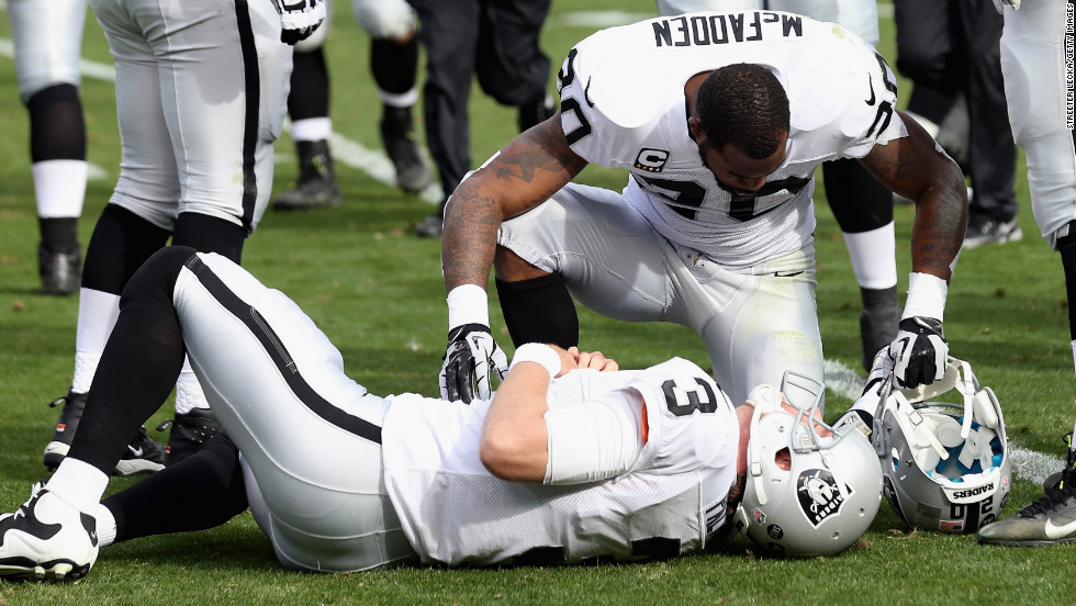 Darren McFadden of the Raiders checks on quarterback Carson Palmer after Palmer was knocked down in the first half against the Panthers on Sunday.