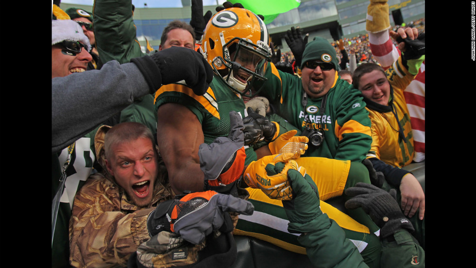 Randall Cobb of the Packers leaps into the stands after scoring a touchdown against the Titans on Sunday.